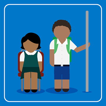 Two school students are sitting on a bus. One is seated and the other is holding onto a handrail.