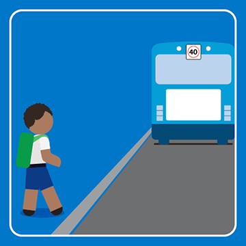 School student waiting for the bus to leave before crossing the road