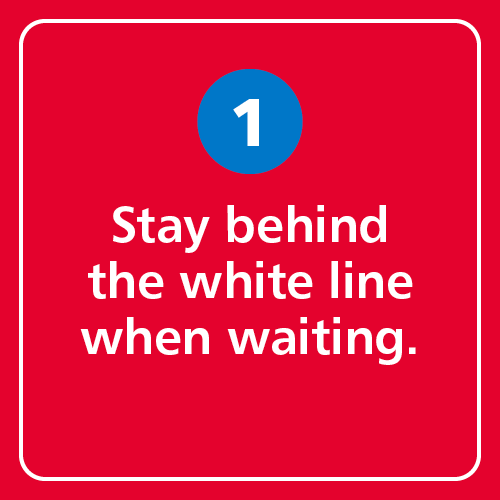 Stay behind the white line when waiting.