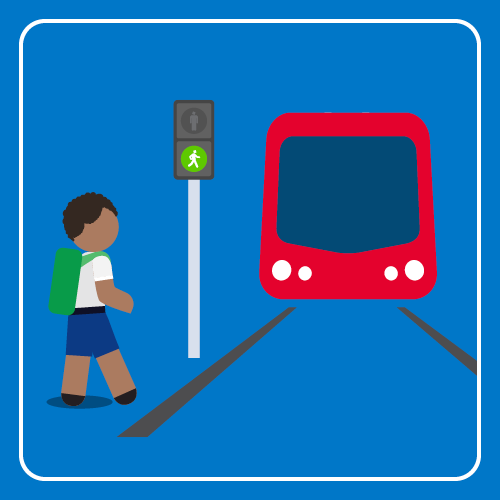 Student is crossing the light rail track on a green walking signal.