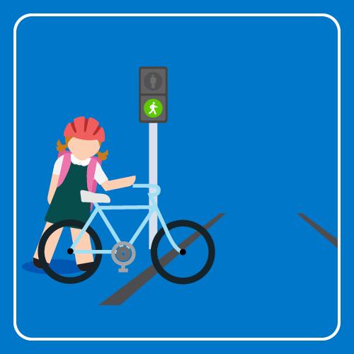 Student is walking a bike across the light rail tracks on a green walking signal.